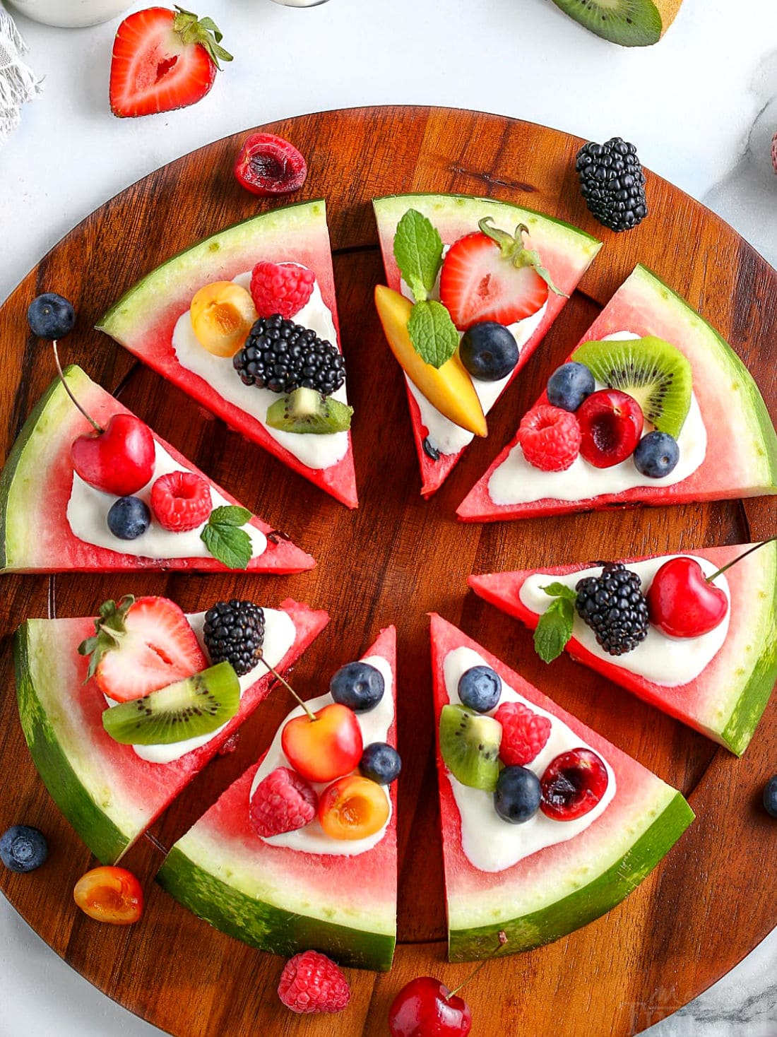 whole watermlon pizza cut into wedges topped with cream cheese glaze and fresh fruit on wood board