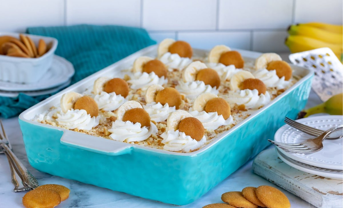 banana pudding in baking dish topped with dollops of whipped cream banana slices and nilla wafers