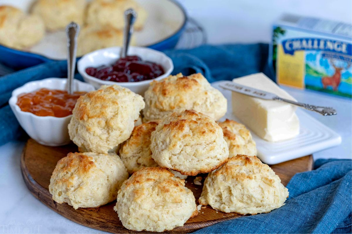 drop biscuits on wood board with jelly and butter