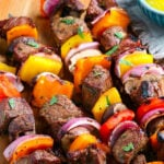 grilled steak kabobs ready to eat on wood plate with text overlay pinterest