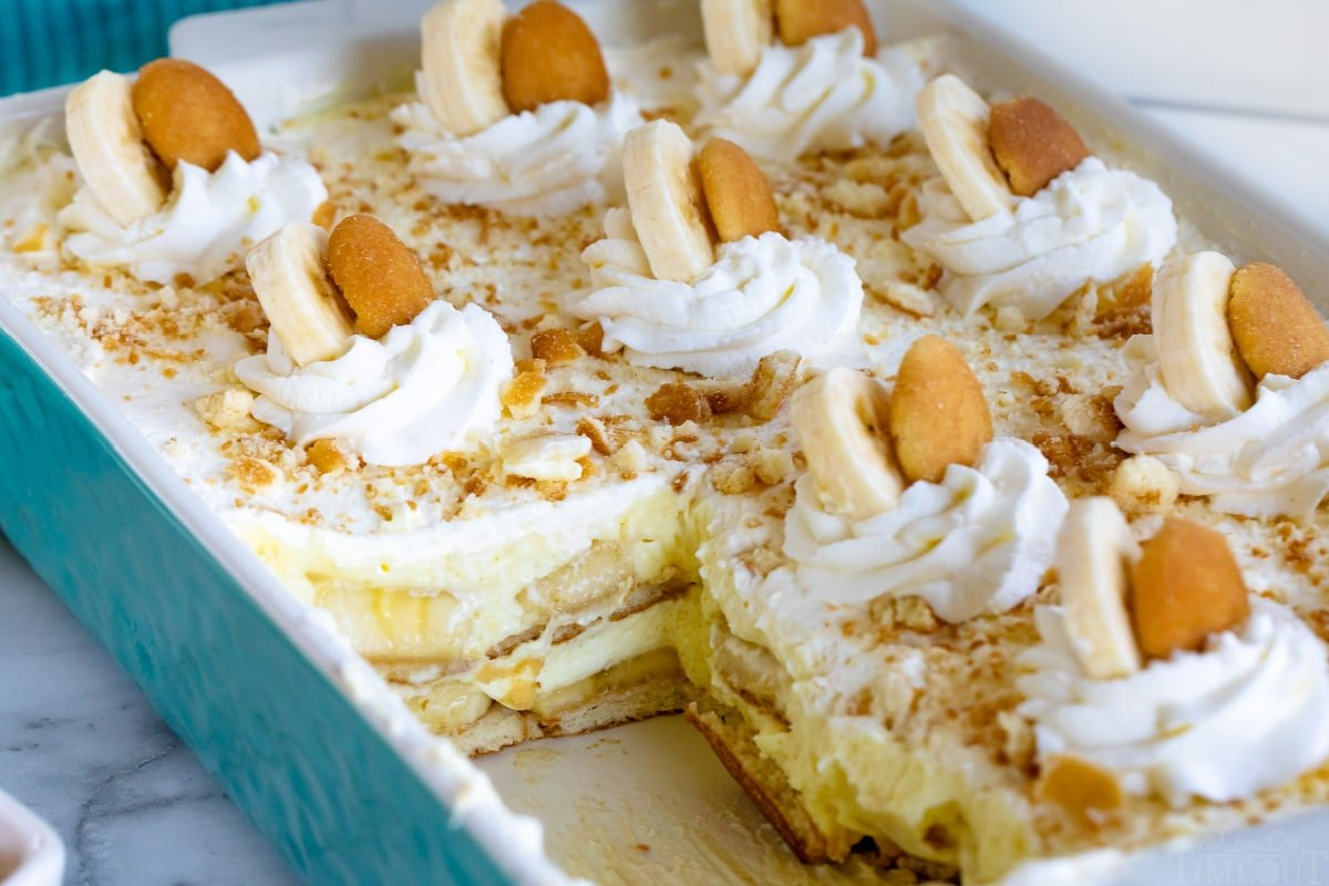 teal casserole dish with banana pudding recipe in it with a few servings removed