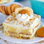 the best banana pudding recipe served on a white plate garnished with whipped cream and nilla wafers