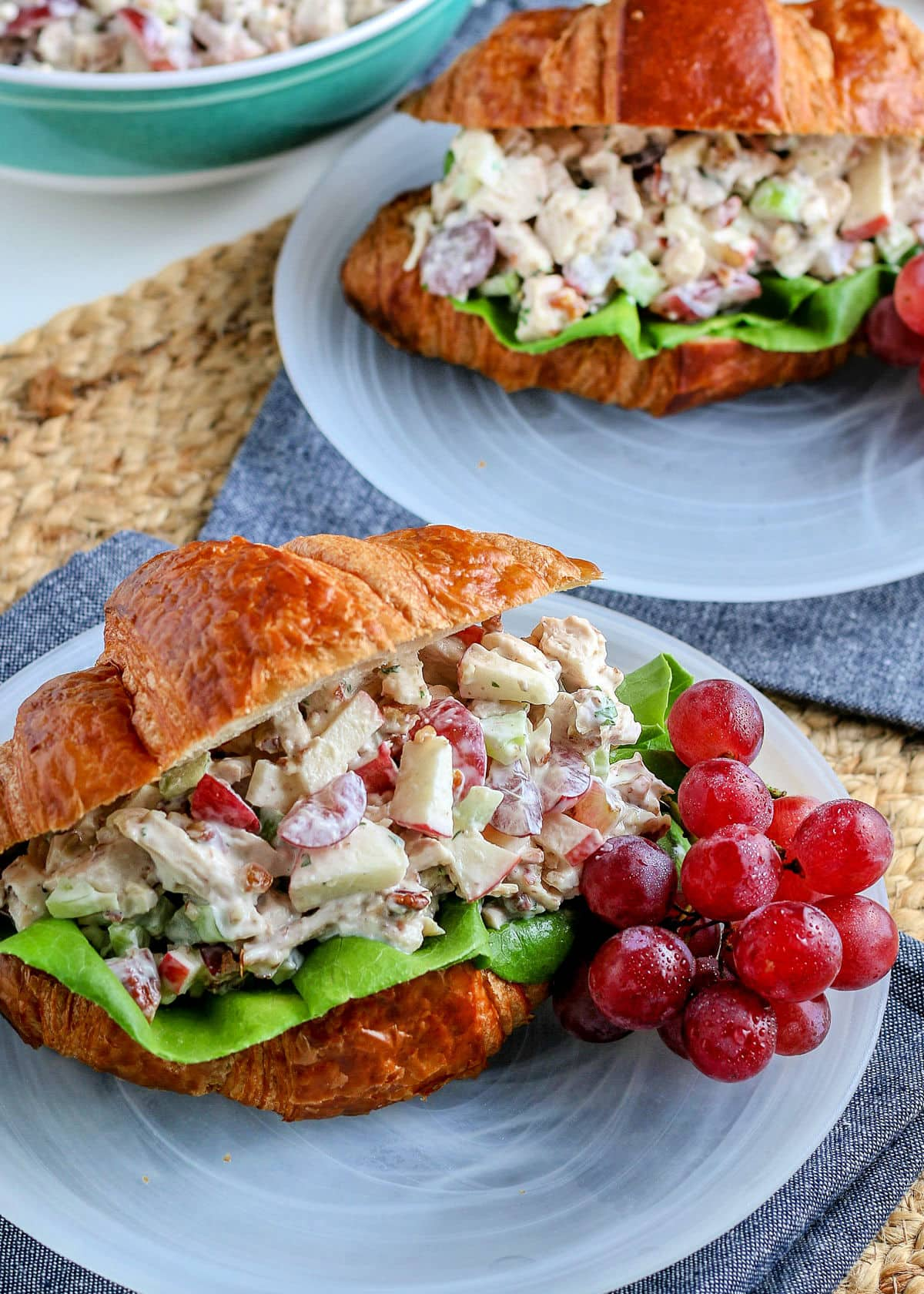 2 chicken salad sandwiches on white plates with blue napkins