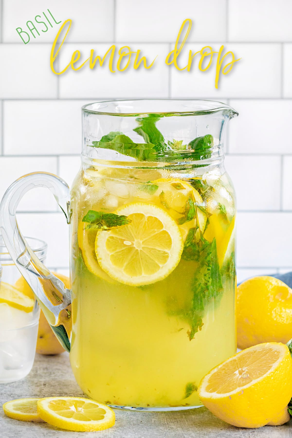 basil lemon drop in glass pitcher with lemon slices in and around pitcher with title overlay
