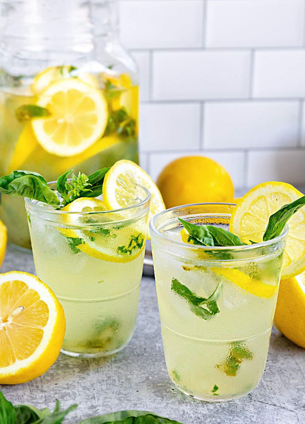 basil lemon drop poured into two glasses with fresh basil and halved lemons table