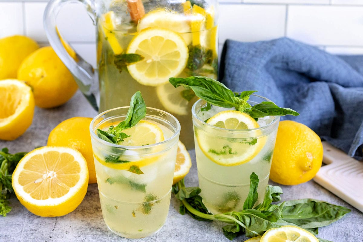 basil lemon drop poured into two glasses with pitcher in the background with basil and lemons scattered about
