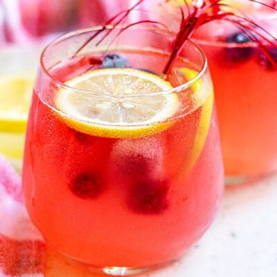 berry lemonade in a wine glass garnished with lemon slices square
