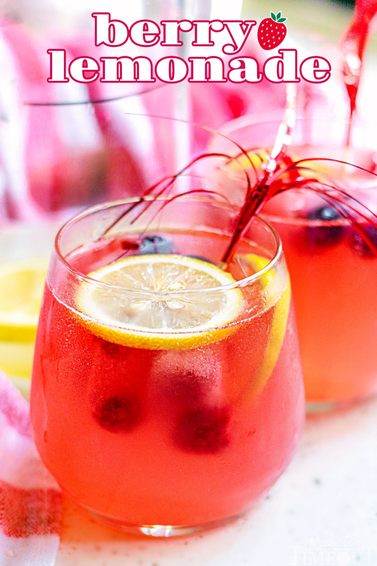 berry lemonade in a wine glass garnished with lemon slices with title overlay