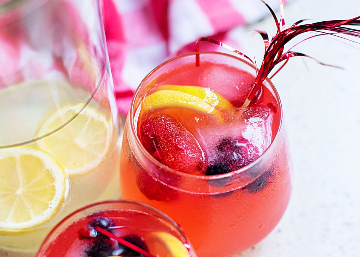 berry lemonade recipe in 2 glasses with lemonade in pitcher on the side