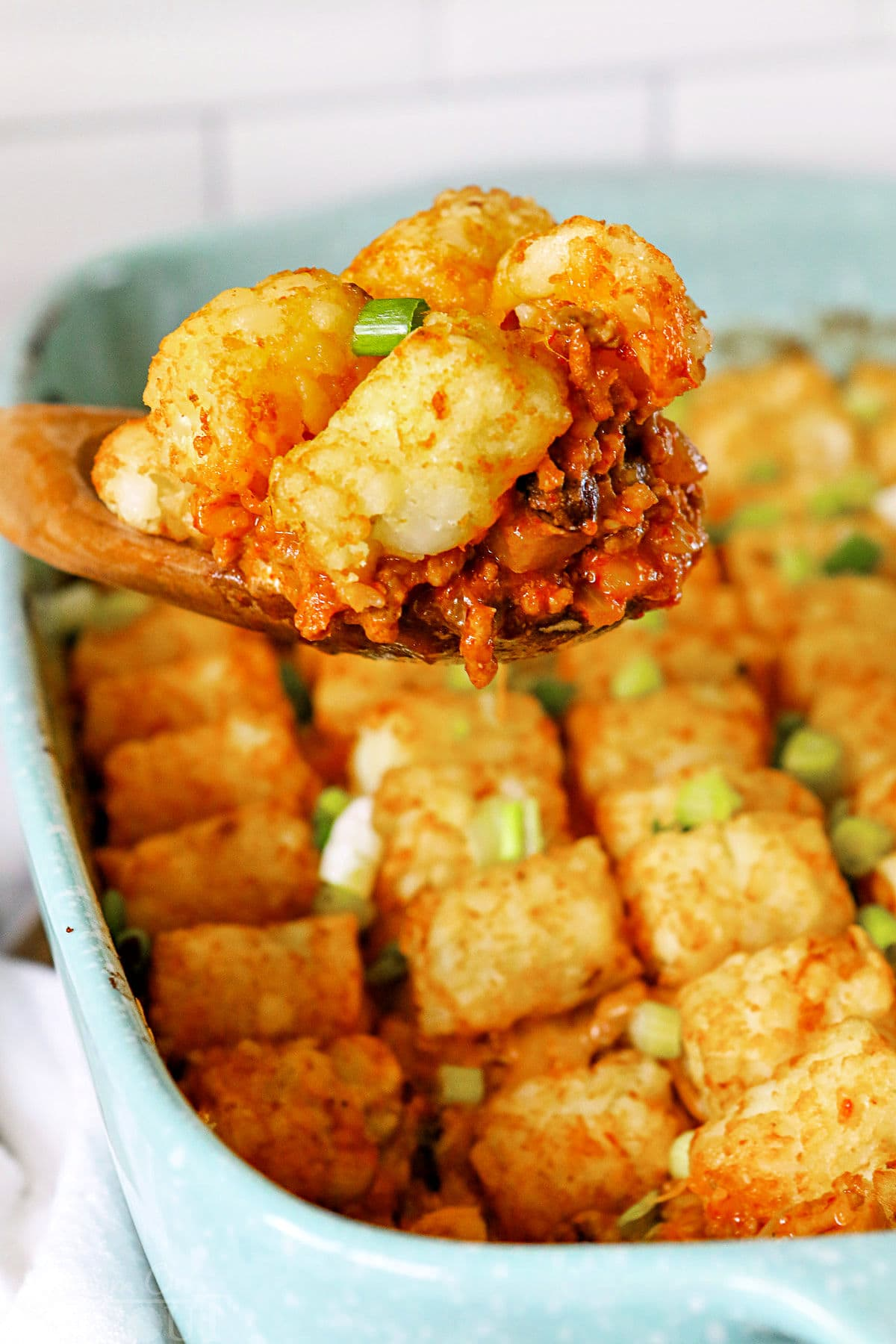 taco tater tot casserole being scooped out of dish with large wood spoon