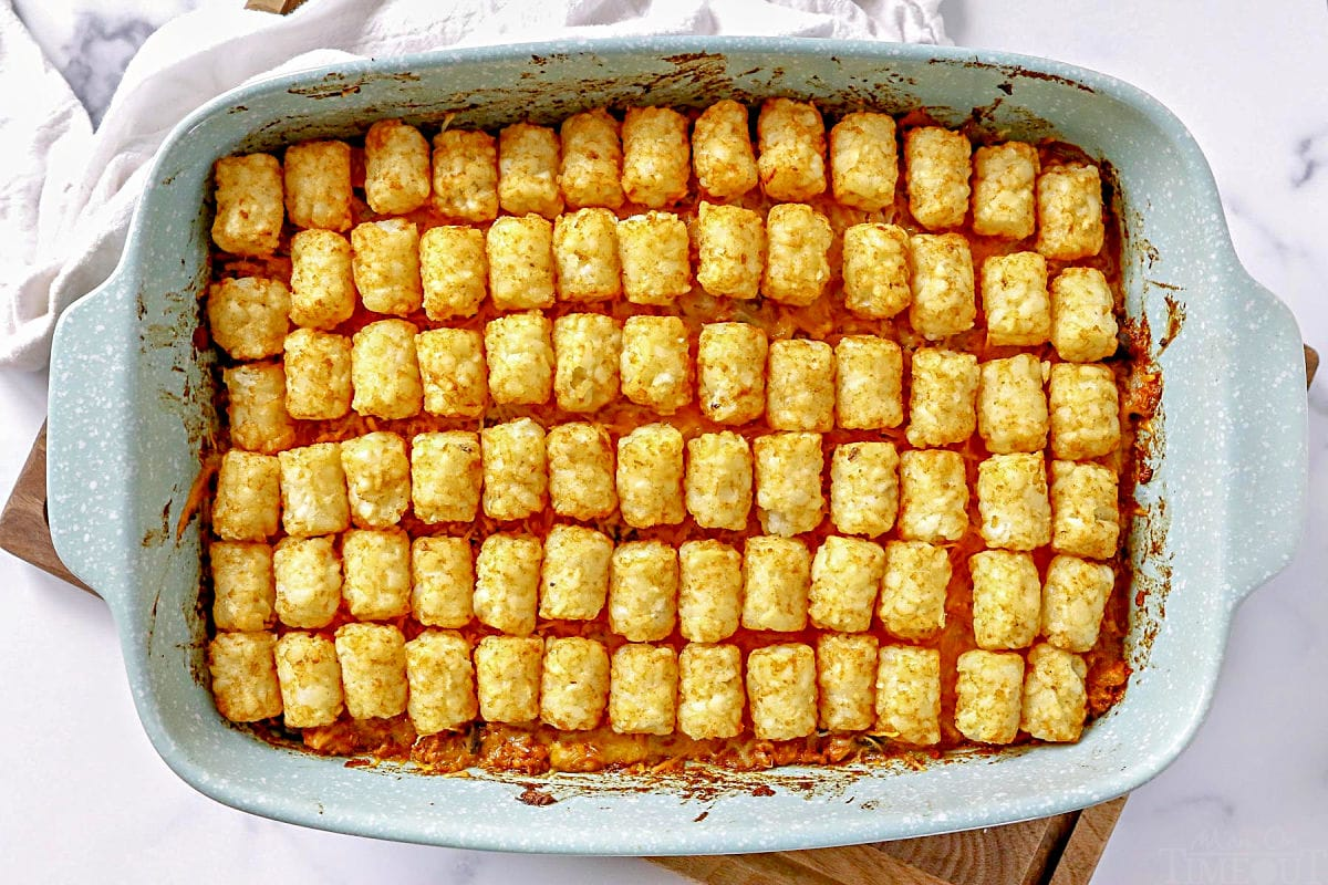 taco tater tot casserole cooked in casserole dish sitting on wood cutting board