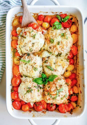 chicken and tomatoes on plate with side salad with casserole dish in background