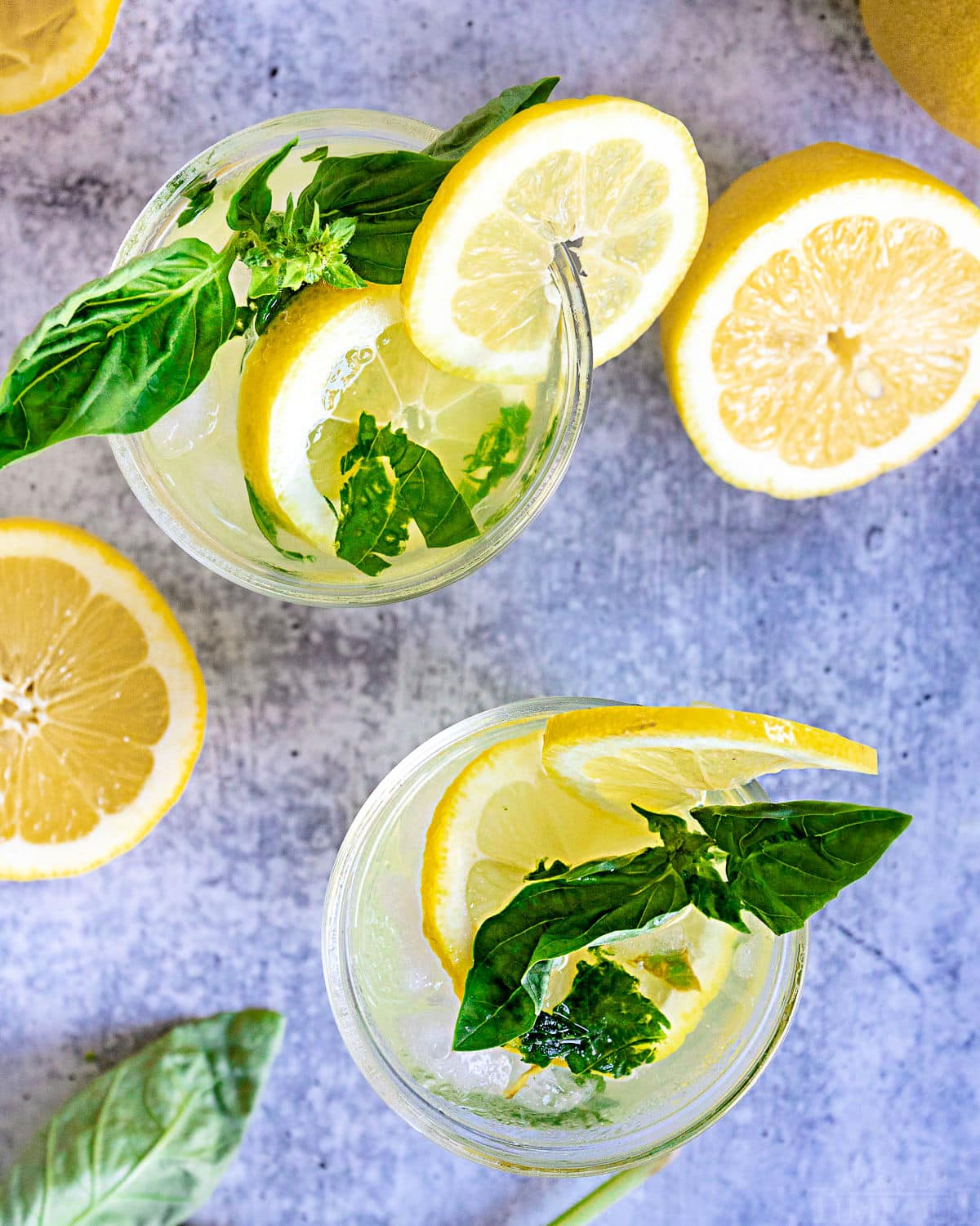 top down view of two glasses with basil lemon drop garnished with fresh basil and lemon slices