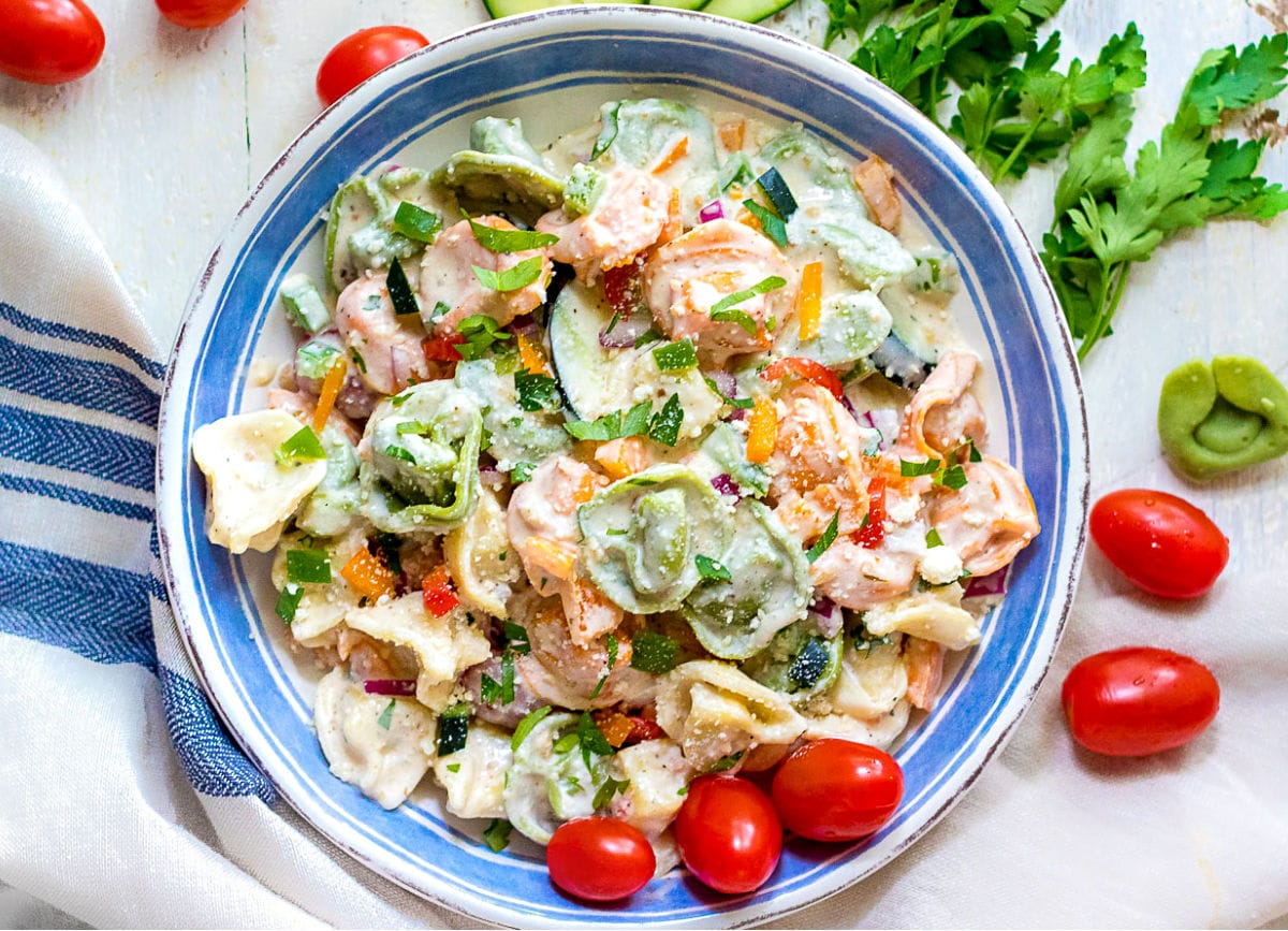 tortellini pasta salad with creamy dressing in white and blue bowl