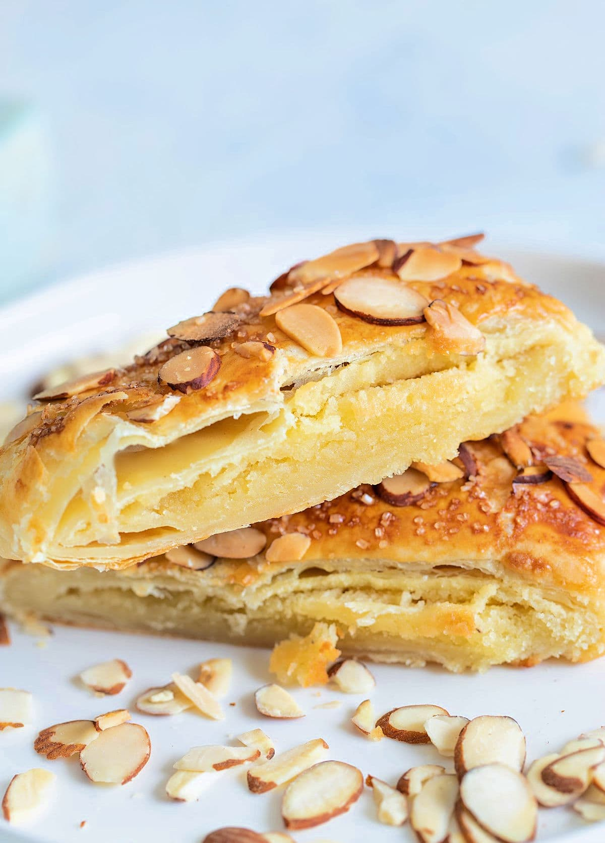 two pieces of Bear Claw pastry on white plate garnished with sliced almonds white background with almond bear claw