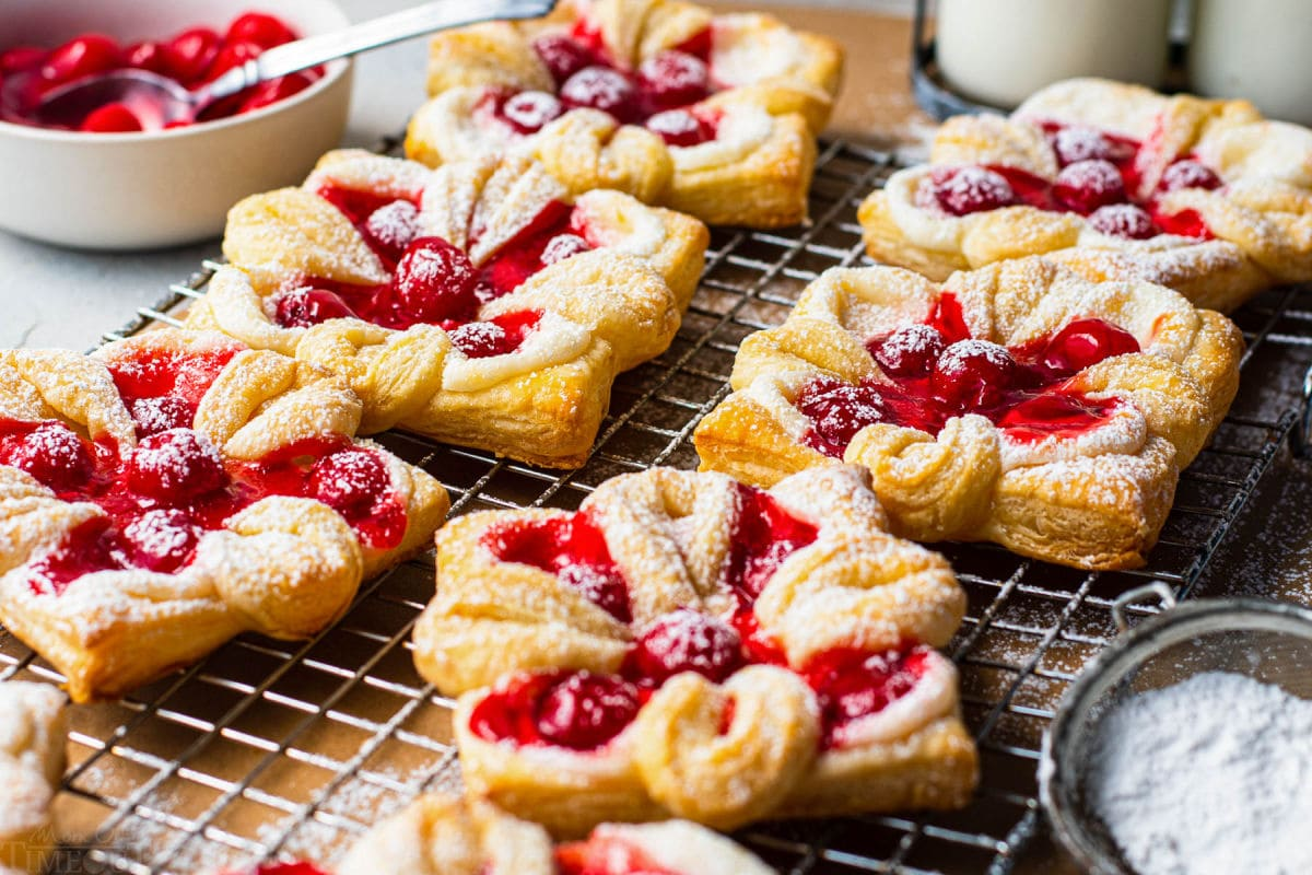 6 danishes with cherries baked and sprinkled with powdered sugar sitting on wire cooling rack