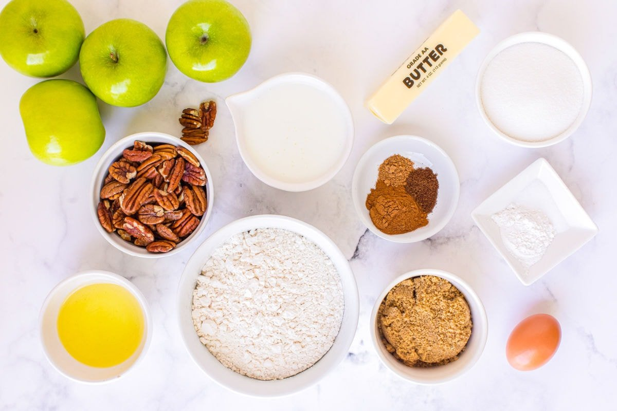 apple muffin ingredients measured out into small bowls sitting on white surface