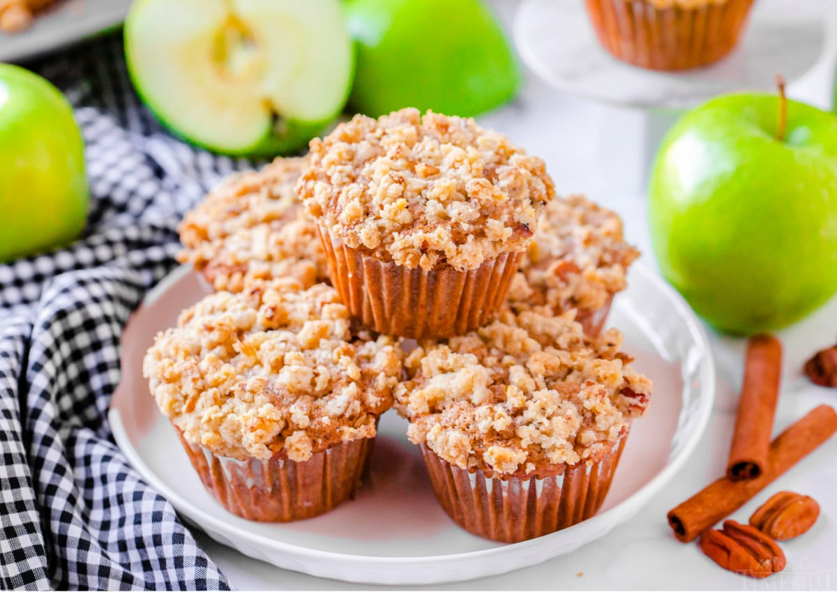 apple muffins stacked on white plate with blue and white napkin beneath the plate apples in the background