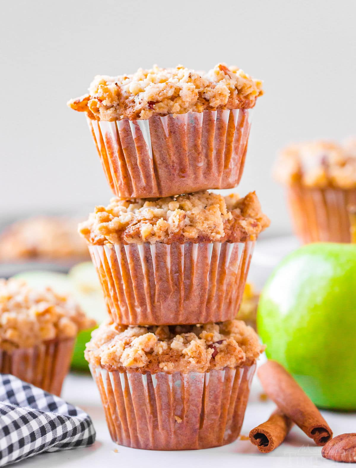 apple muffins-stacked three high with more muffins in background