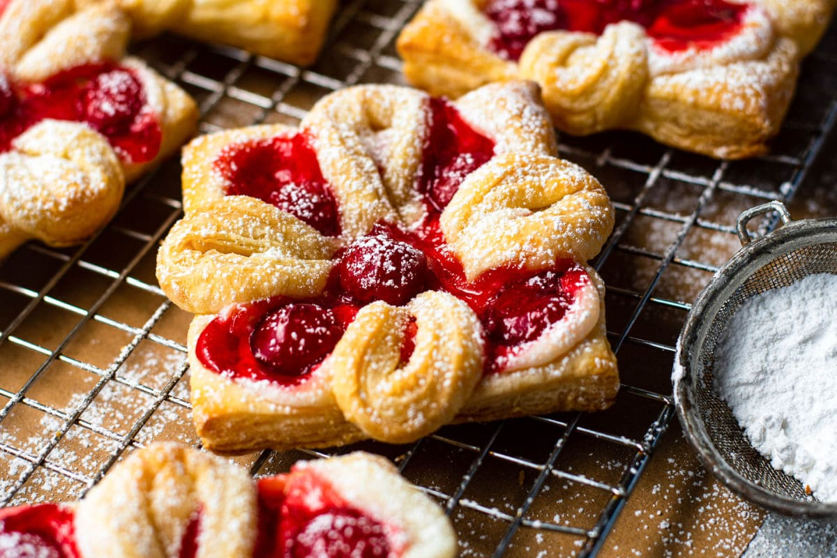 cheese danish with cherries baked and sprinkled with powdered sugar sitting on wire cooling rack