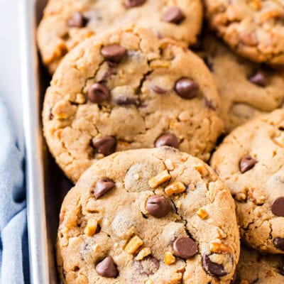 chocolate chip cookies piled in small silver tray with blue napkin on the side