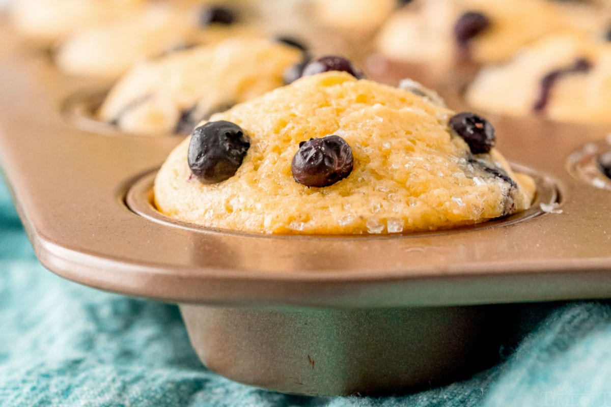 close up of corn muffin in muffin tin with blue napkin underneath the pan