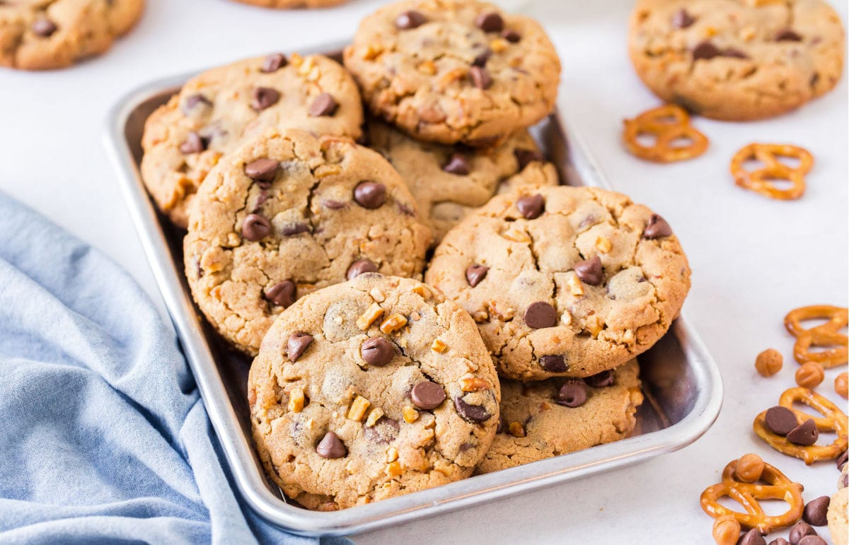 lots of cookies in small metal sheet pan piled on top of each other with blue napkin on the side