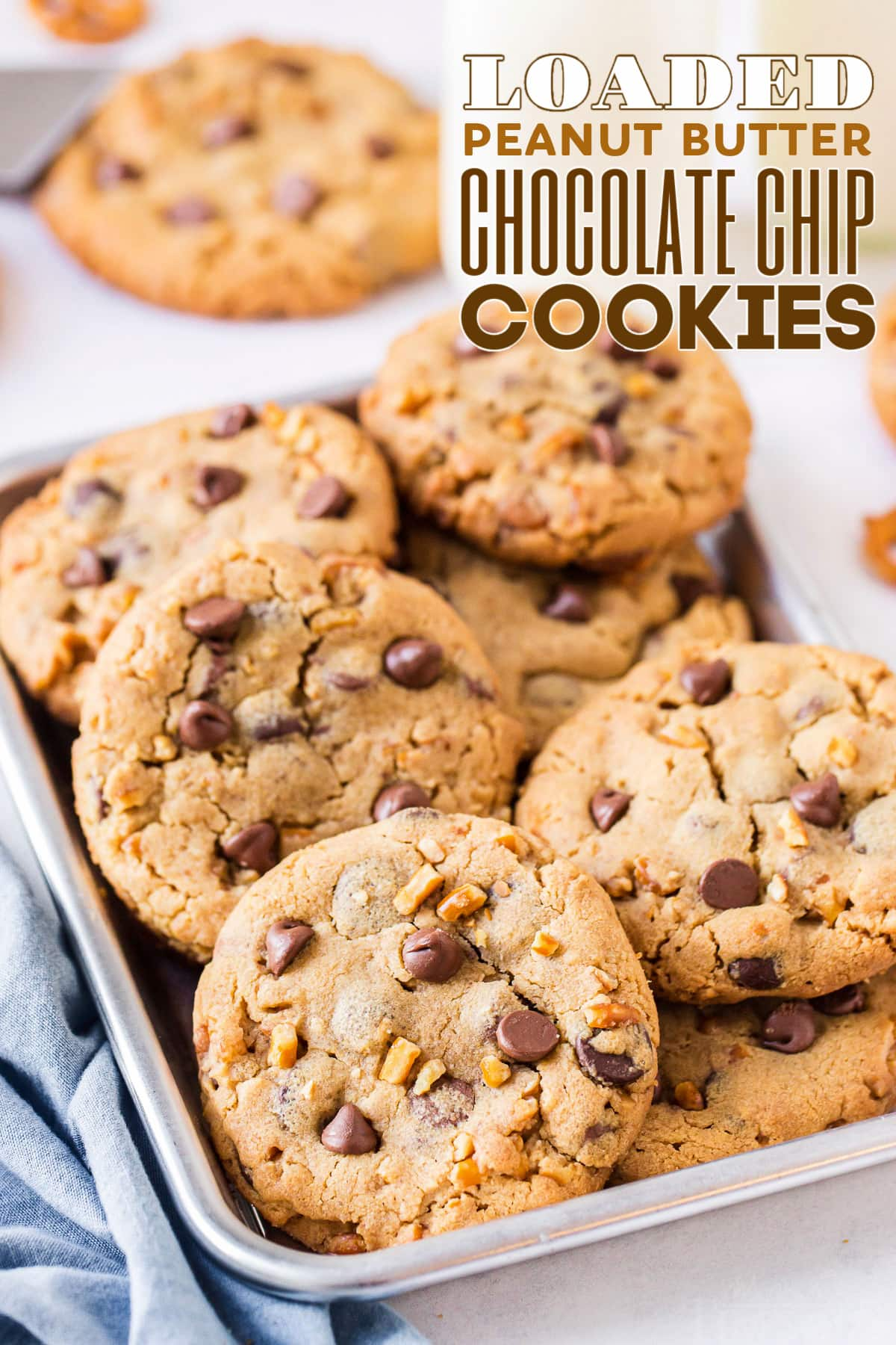 pile of loaded peanut butter chocolate chip cookies in eigth sheet pan with blue napkin front and text overlay at top