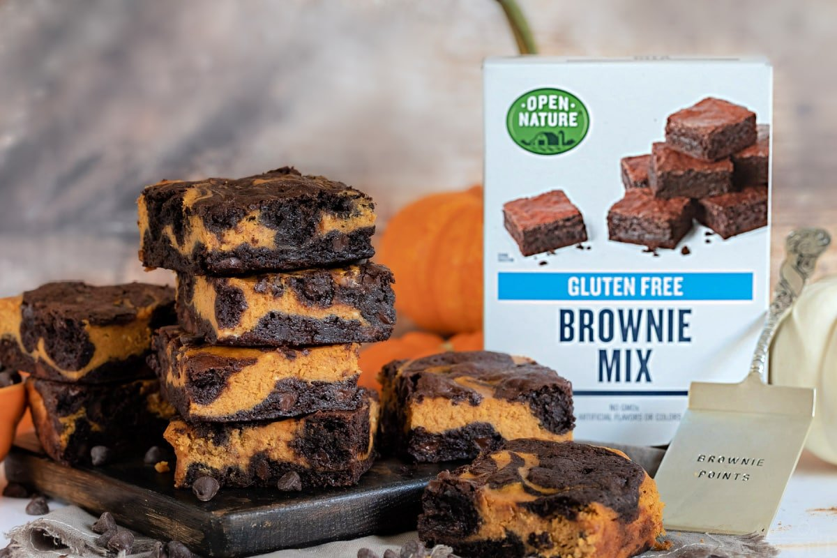 pumpkin brownies on wood board with brownie mix box on the side