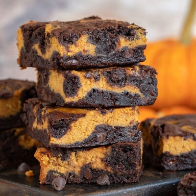 pumpkin brownies stacked 4 high on dark wood board with pumpkin in background