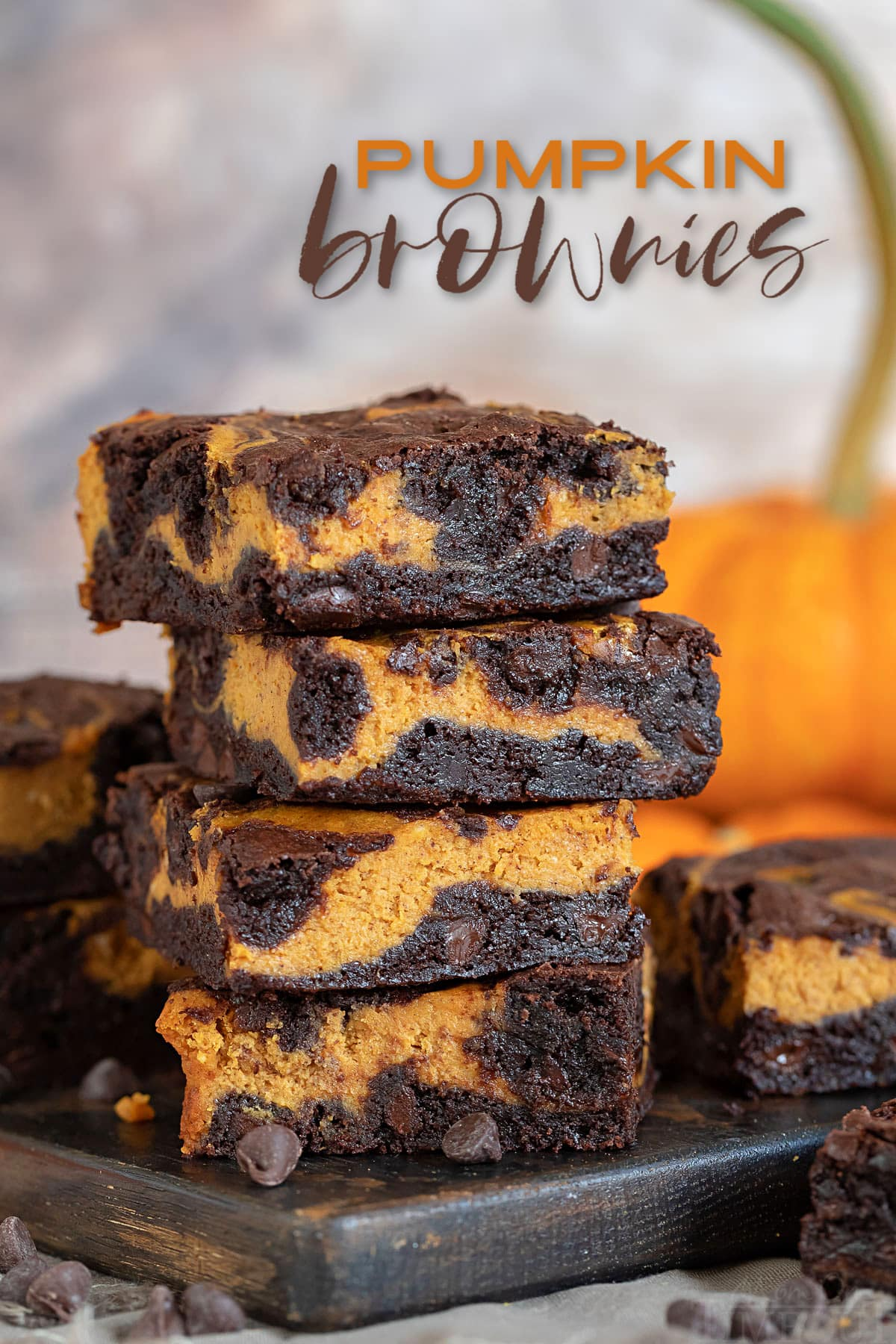 pumpkin brownies stacked 4 high on dark wood board with pumpkin in background and with text overlay