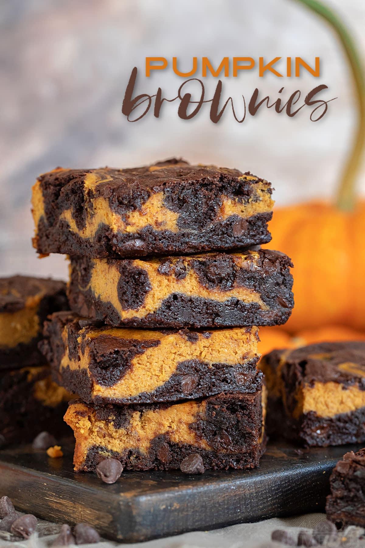 pumpkin brownies ułożone 4 wysoko na desce z ciemnego drewna z dynią w tle i z nałożonym tekstem