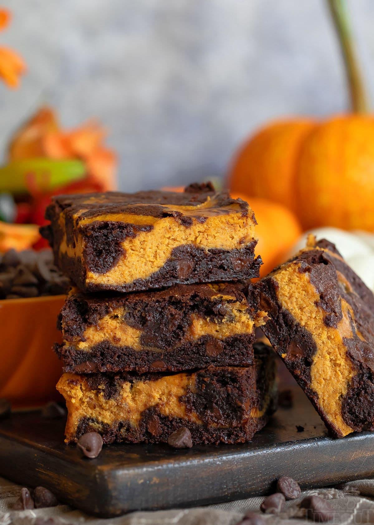 pumpkin brownies ułożone po trzy na desce z ciemnego drewna z dynią w tle