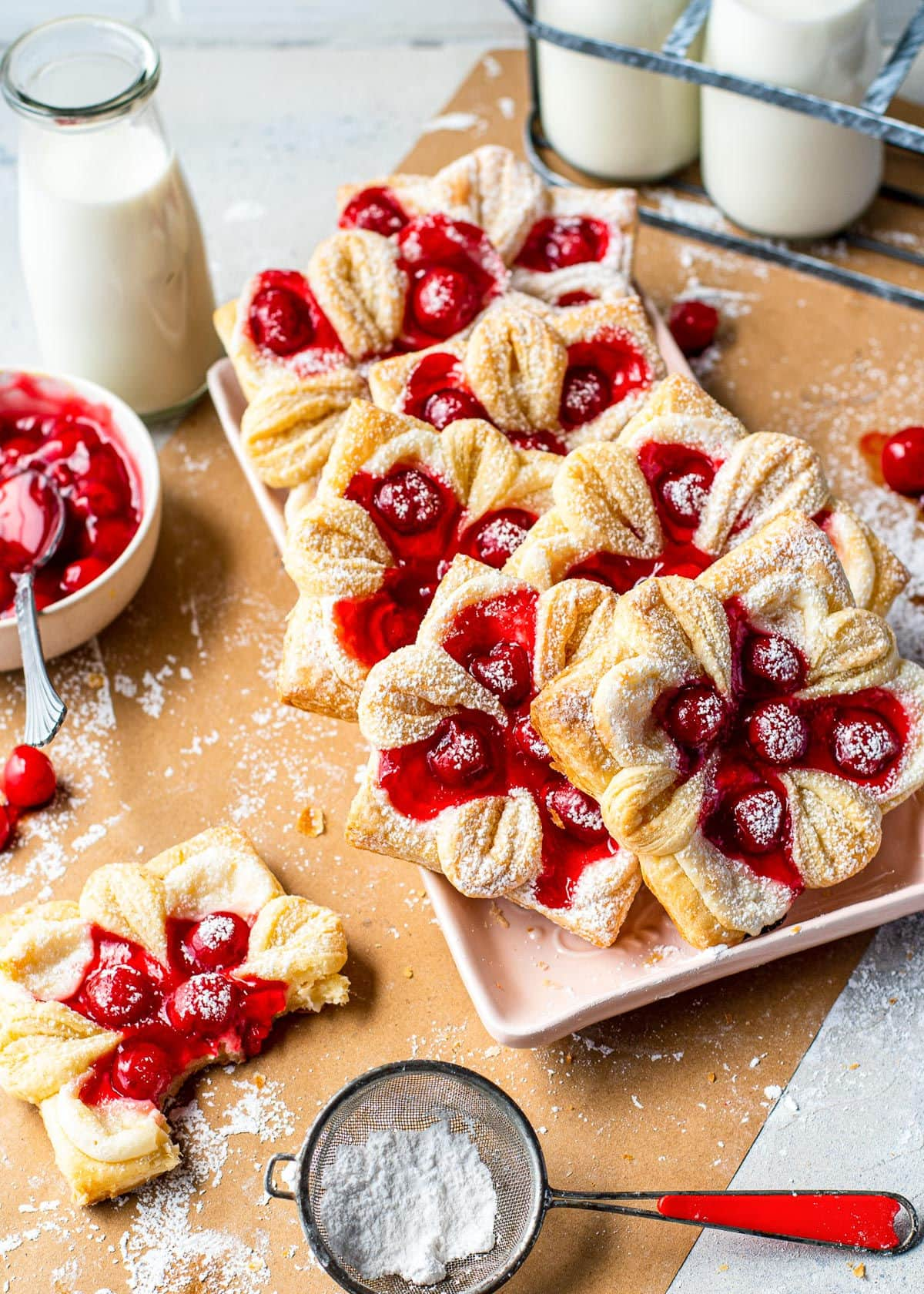 top down view of all of the cheese danishes with cherries on a tray and with powdered sugar