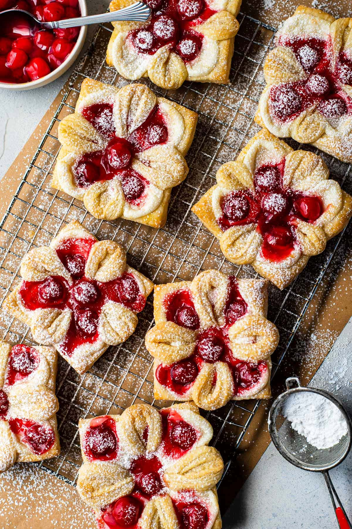 top down view of cherry danishes on brown parchment paper with powdered sugar sprinkled over the top