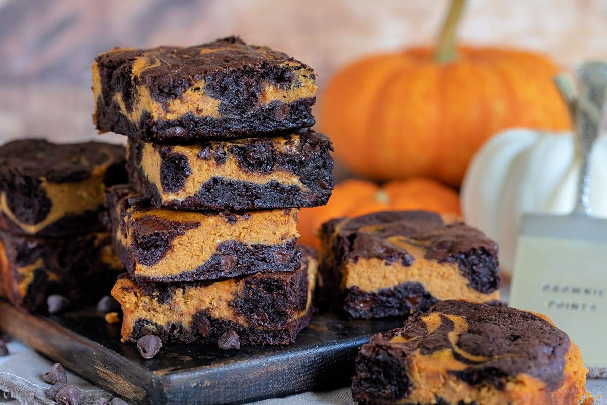 foto amplia de los brownies de tarta de queso y calabaza sobre una tabla oscura con calabazas de fondo