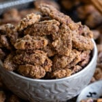candied pecans in small gray bowl on baking sheet with more pecans