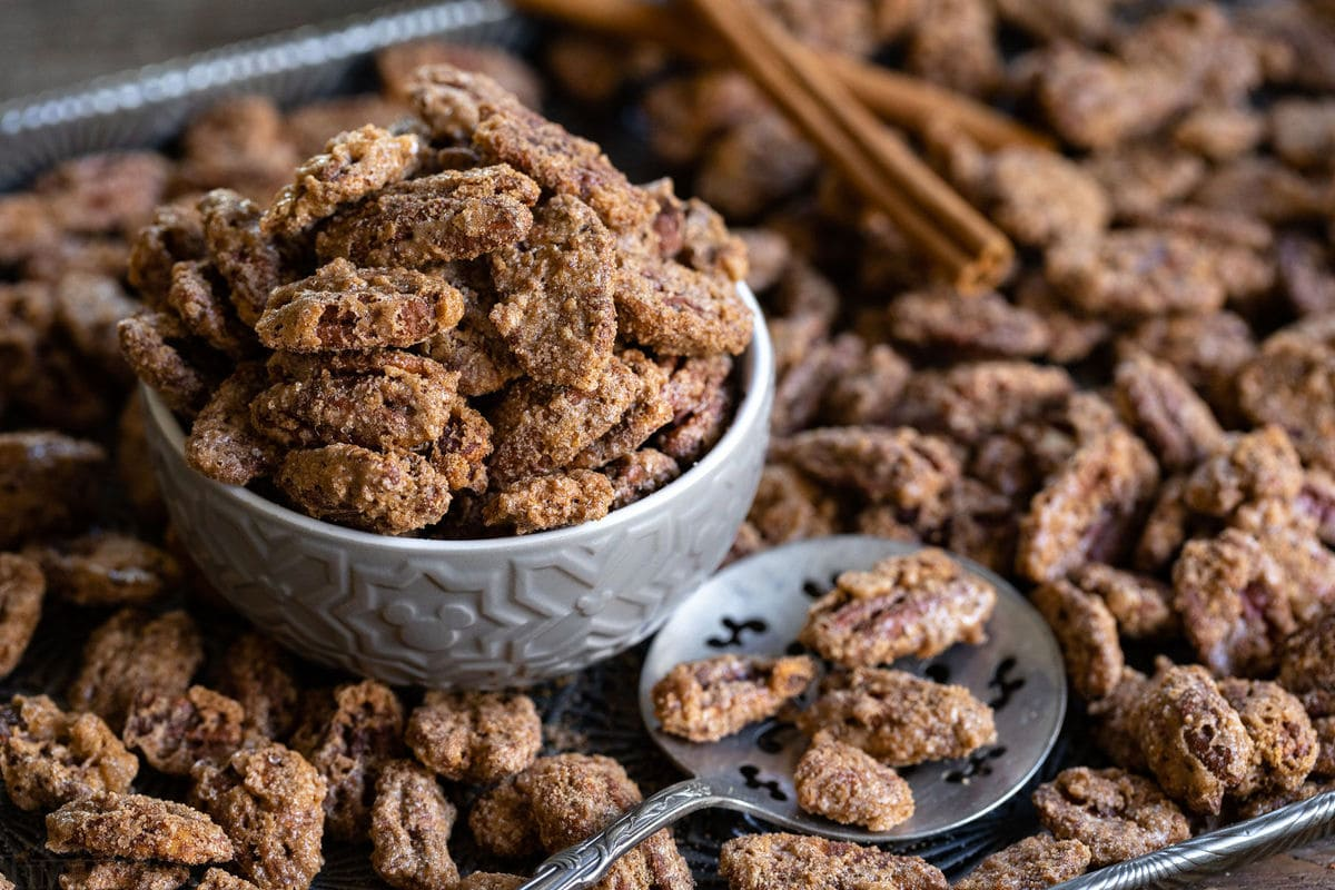 candied pecans in small bowl sitting on antique baking sheet with spoon and lots of candied pecans strewn about