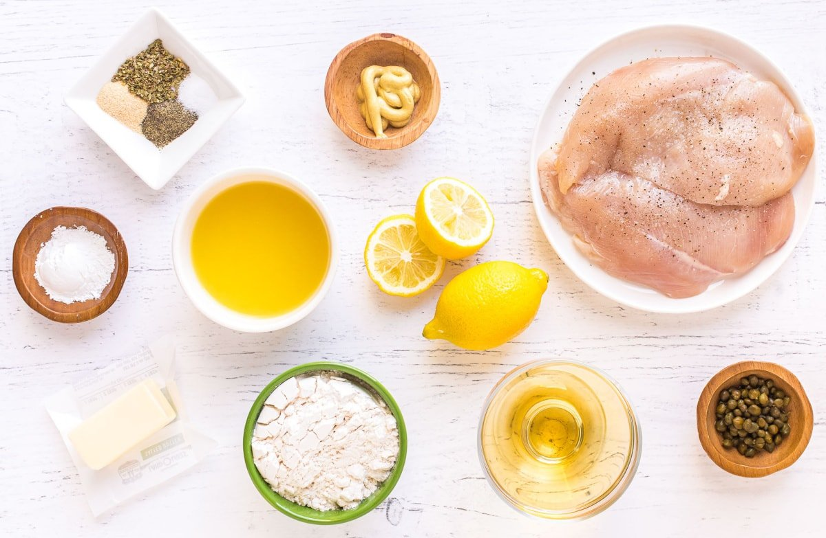 chicken piccata ingredients set out in small bowls and plates on white surface