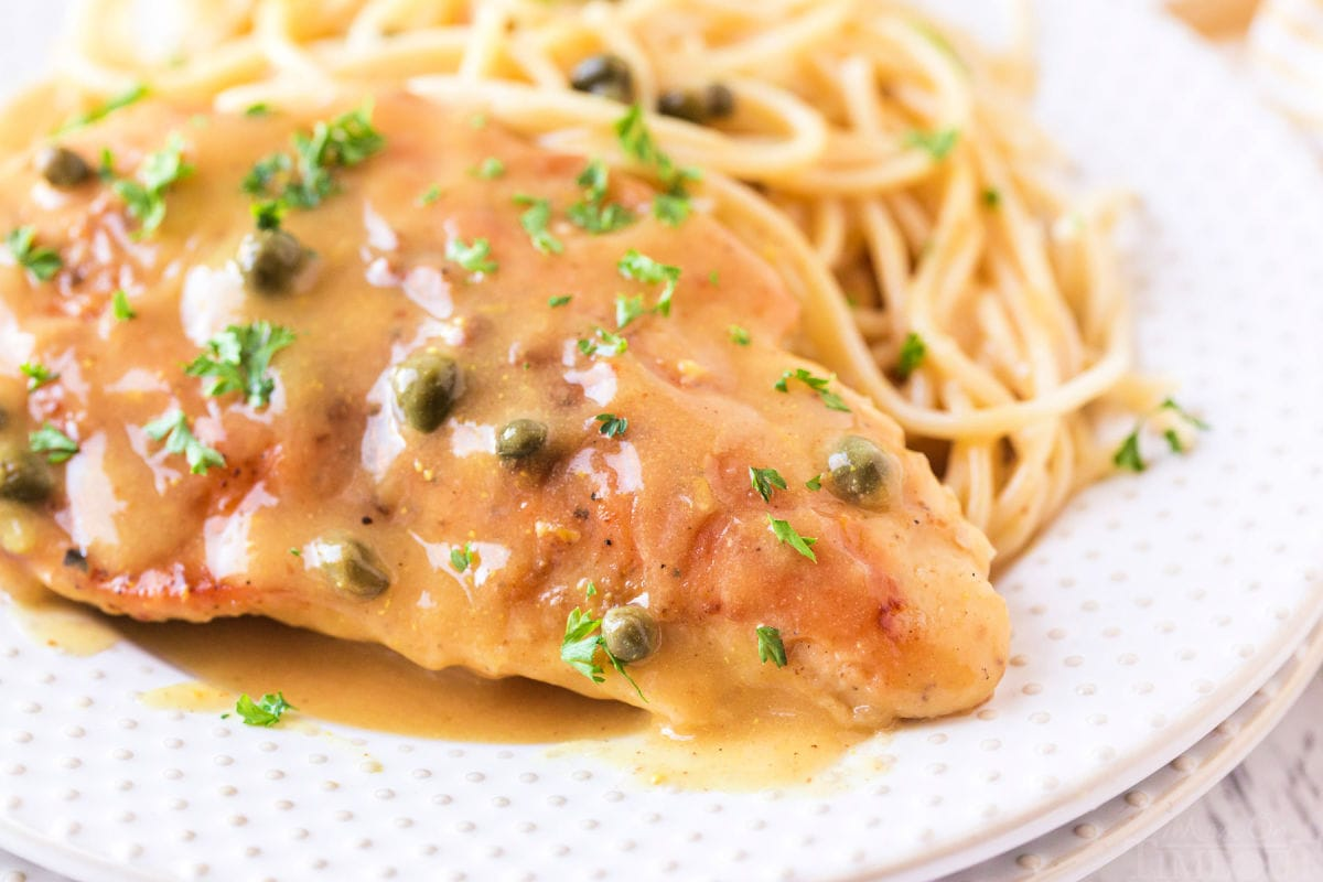 close up of chicken piccata on plate with parsley on top