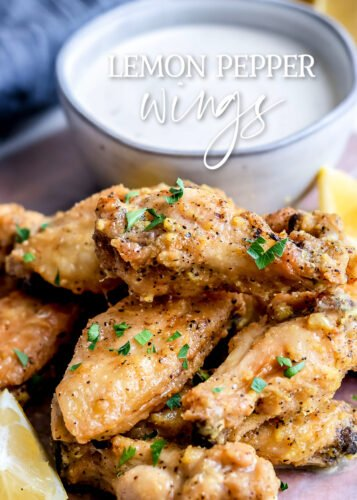 crispy baked chicken wings garnished with lemon pepper sauce and parsley small bowl of ranch in back