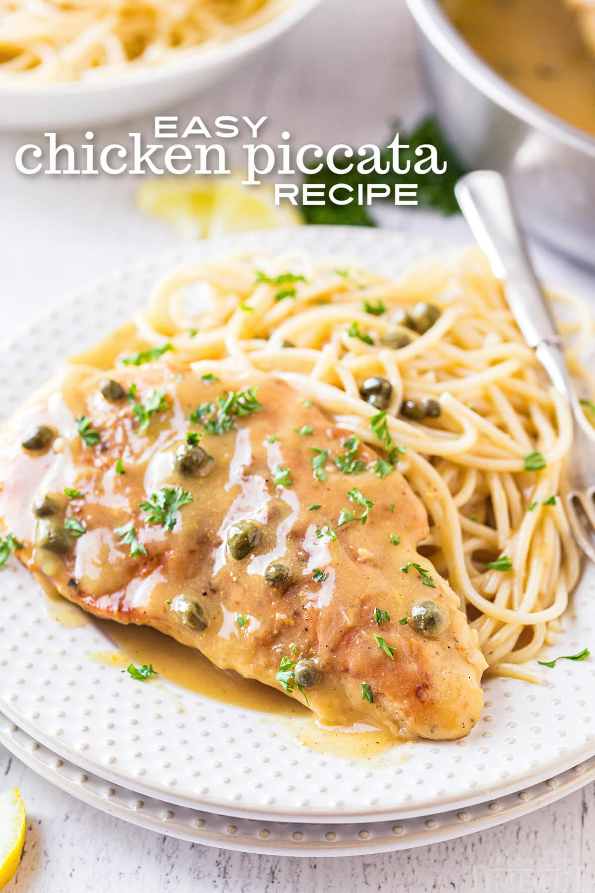easy chicken piccata recipe plated on a white plate with spaghetti and garnished with parsley
