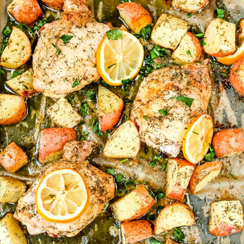 greek chicken prepared on sheet pan with lemons potatoes and parsley