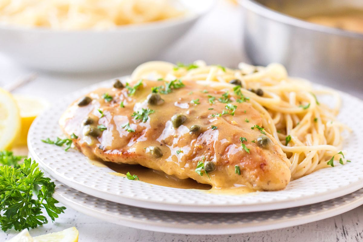 lemon chicken piccata recipe on white plate with spaghetti on the side and parsley garnish