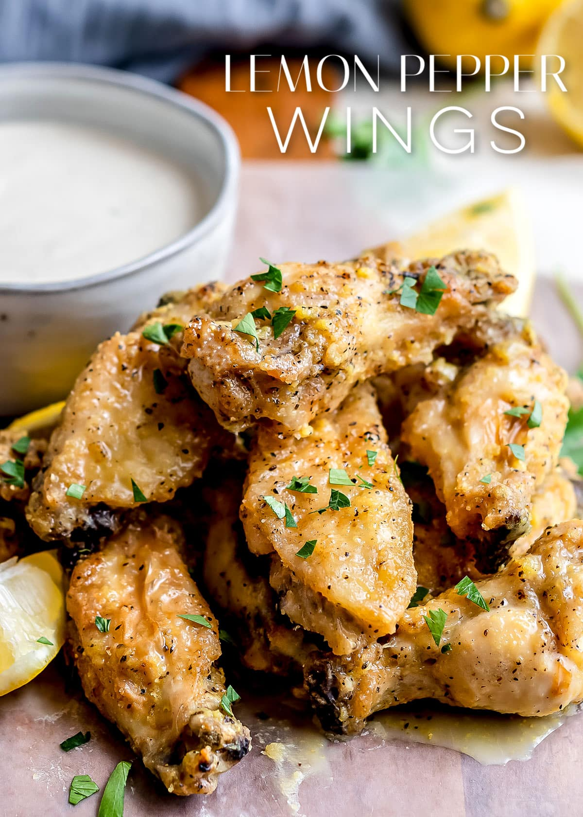 lemon pepper wings stacked in a pile with a bowl of ranch behind them and title overlay at the top
