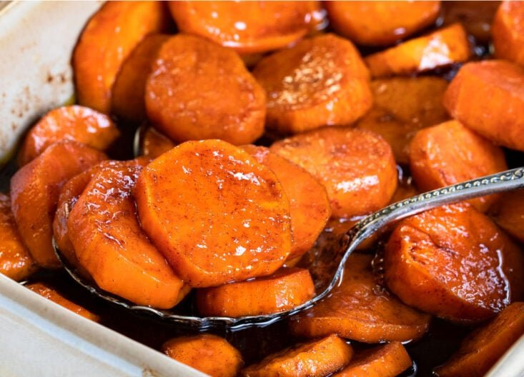 spoonful of candied sweet potatoes in beige baking dish