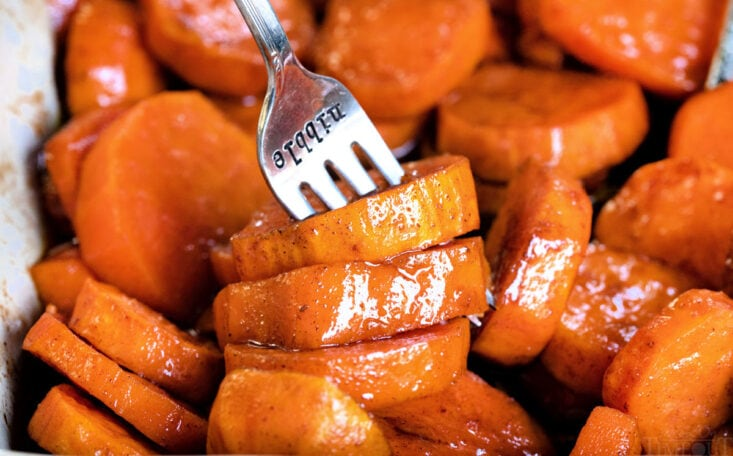 candied yams in baking dish with fork in it