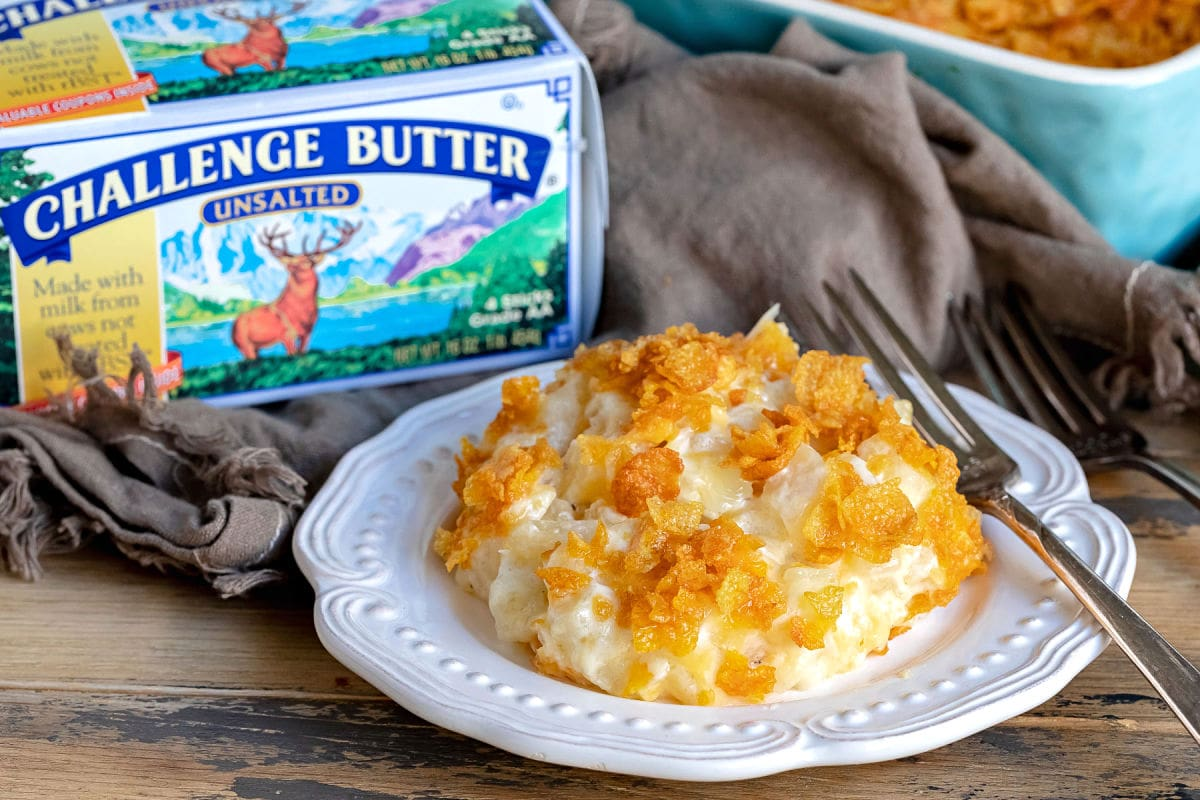 cheesy potatoes on white plate with challenge butter box behind it