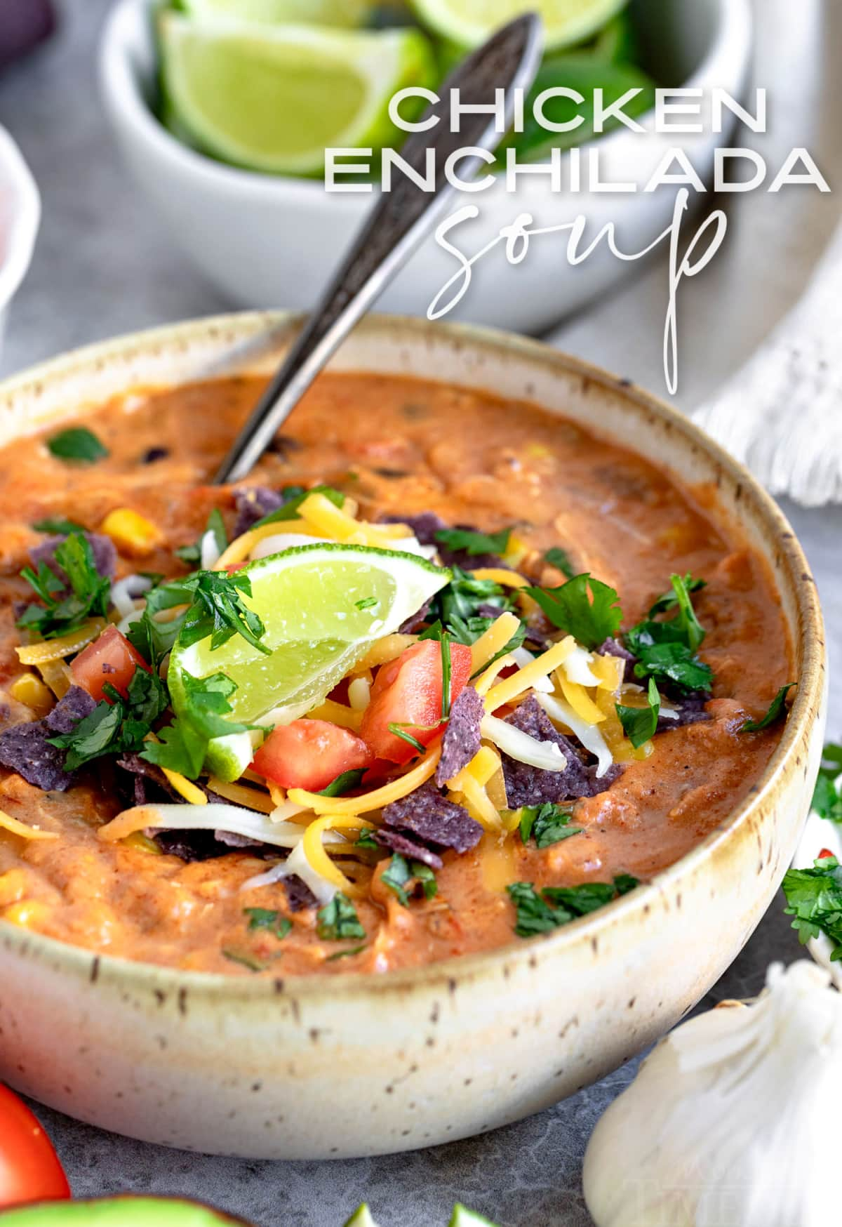 chicken enchilada soup in pottery bowl with spoon and garnished with cilantro lime tomatoes cheese and title overlay at top