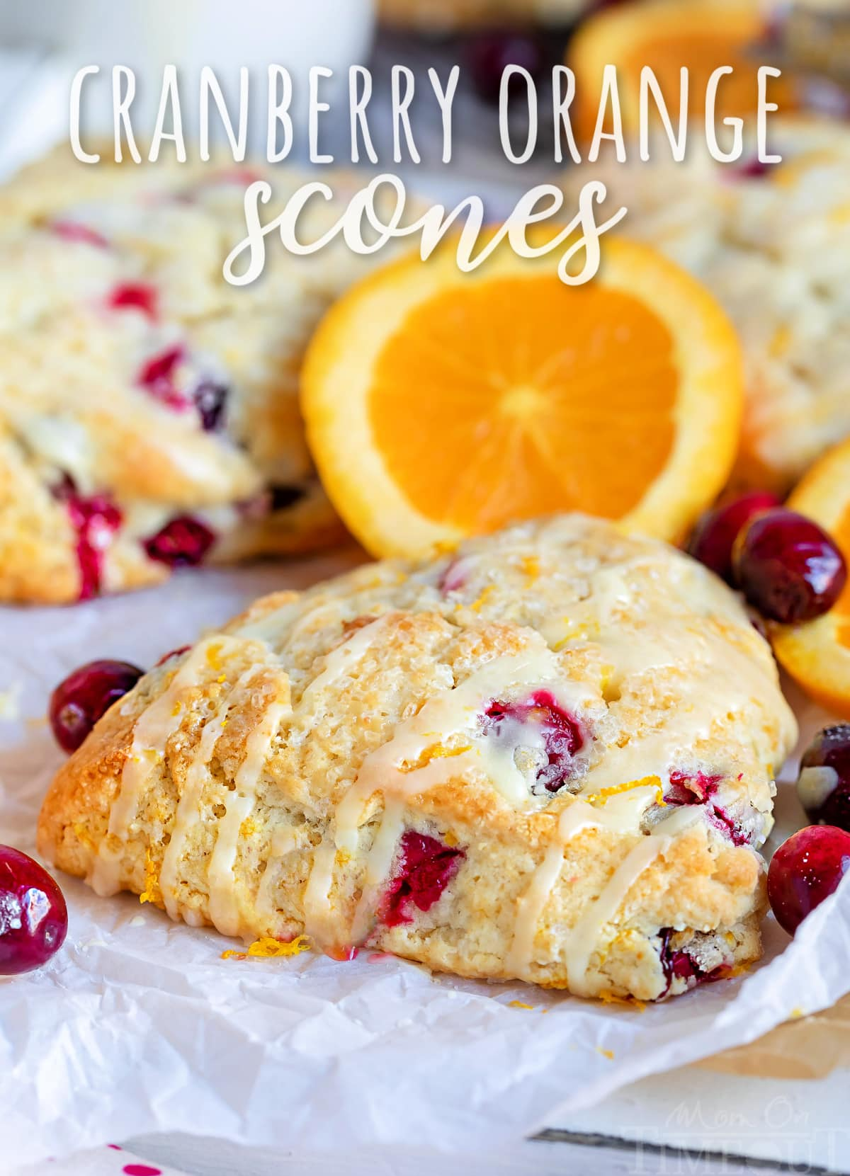 cranberry orange scone sitting on parchment paper with orange glaze drizzled on top with text overlay at top of image